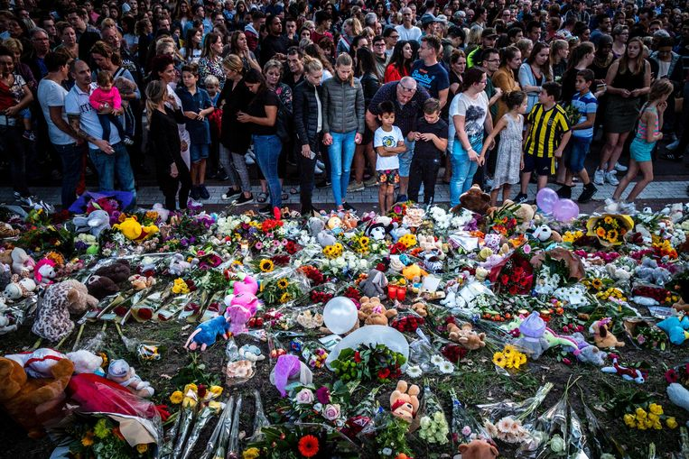 Honderden mensen leggen bloemen nabij de spoorwegovergang aan de Braakstraat in Oss, waar bij het ongeluk vier kinderen omkwamen. Beeld ANP