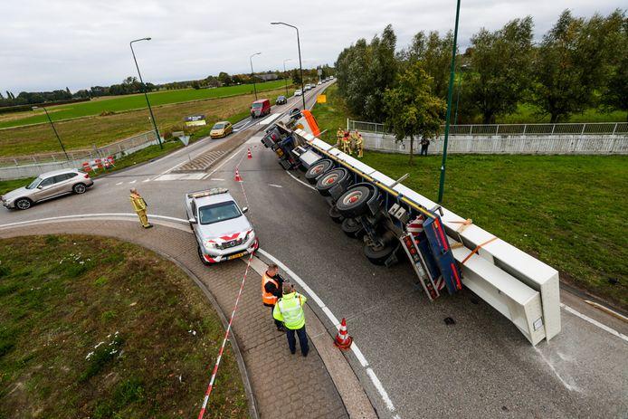 Vrachtwagen kantelt op rotonde met 30 ton staal op trailer in Beek en Donk.