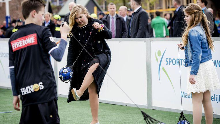 Prinses Alexia en prinses Amalia doen een spel met een bal tijdens Koningsdag in Zwolle. Beeld null