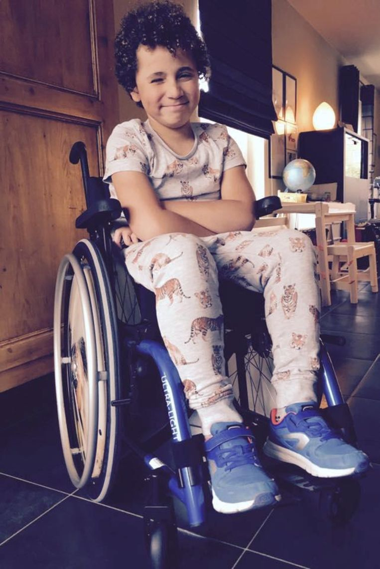 """Jimmy Chapman (8) zit al enkele maanden in zijn rolstoel, maar blijft glimlachen. """"Hij is een ontzettend sympathiek jongetje"""" , zeggen Esthel en Dennys."""