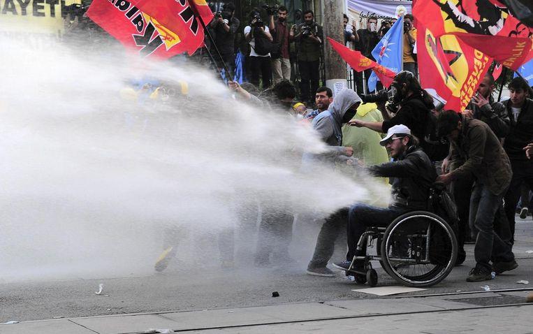 De politie zet het waterkanon in. Zelfs een gehandicapte man moet het ontgelden.