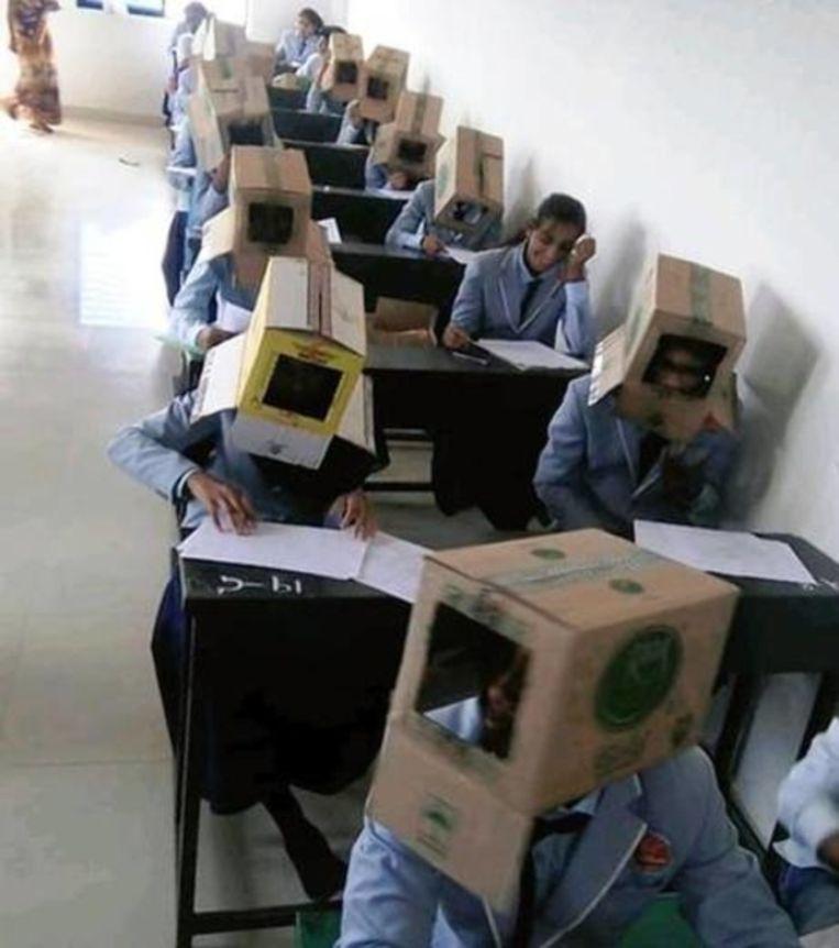 De leerlingen met anti-spiekdozen op hun hoofd. Beeld