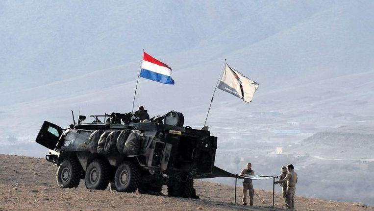 Uruzgan, 2010: Nederlandse militairen in de Chora-vallei zetten een tent op nabij hun Bushmaster. Beeld afp