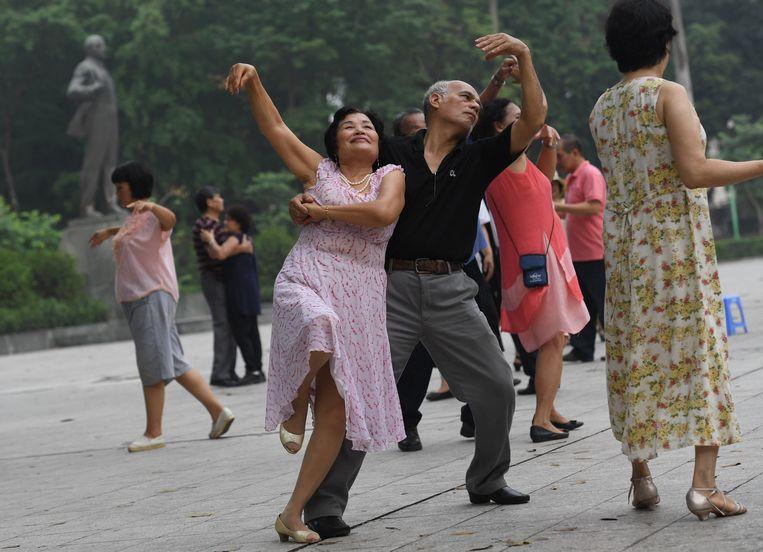 Dansers voor het standbeeld van Vladimir Lenin in het Lenin Park. Beeld AFP