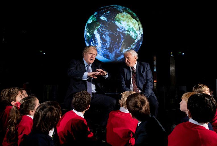 De Britse premier Johnson met programmamaker David Attenborough tijdens een conferentie over de klimaattop in het Verenigd Koninkrijk, in februari. Beeld Reuters