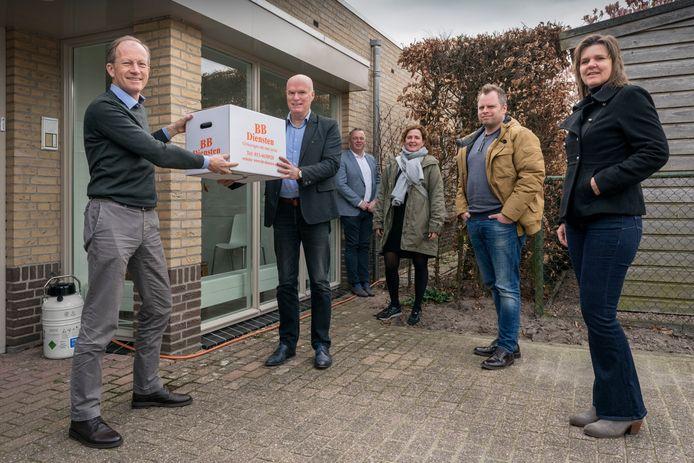 Marc Schoutens overhandigt de doos met mondkapjes aan huisarts Eric Hoomans (links). Verder vlnr wethouder Peter van Steen, Ellen Willink, Marcel Vermeulen en Astrid van Rooij.