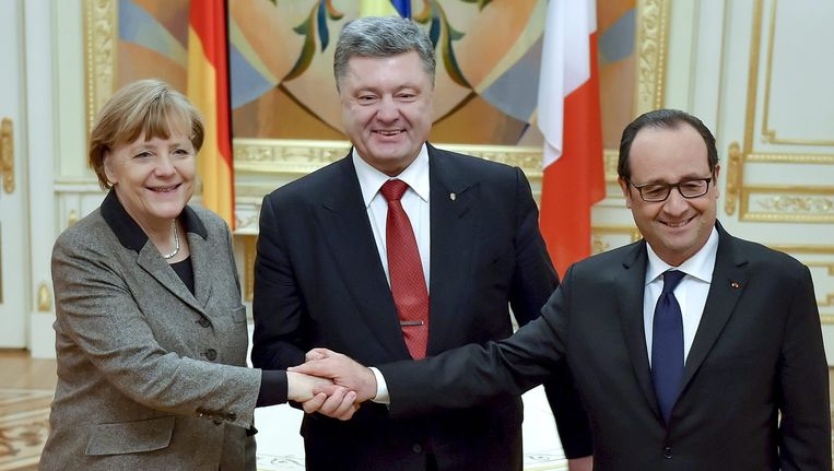 Angela Merkel, François Hollande en Petro Porosjenko schudden elkaar de hand.