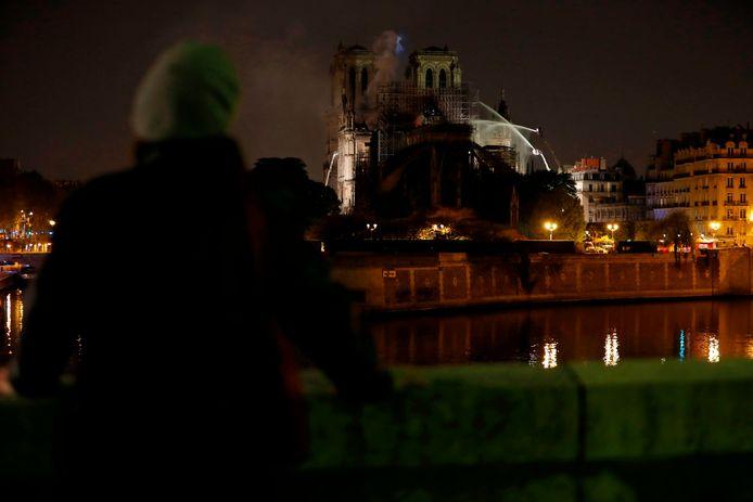 Vanaf de overkant van de rivier de Seine kijkt een vrouw naar het vuur op het 'eiland' in de Seine.