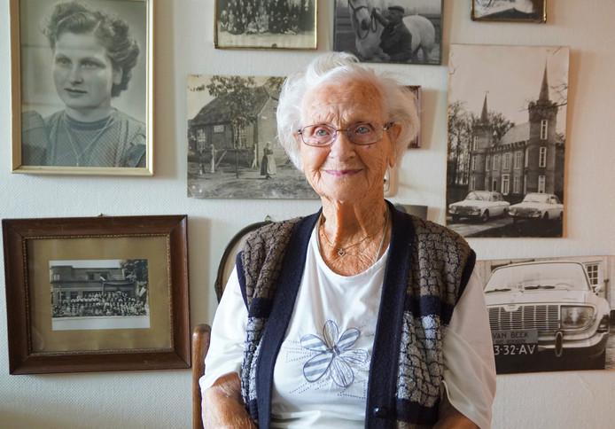 Mevrouw Tonnie van Beek voor de fotomuur met mooie herinneringen.