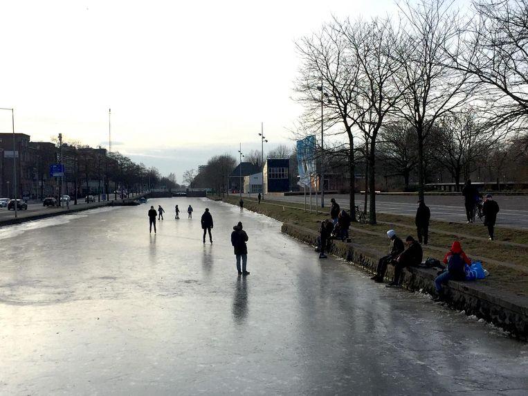 Mensen lopen op het ijs van de Haarlemmervaart Beeld Jan 't Hart