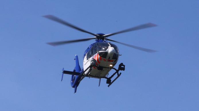 Boven de Waal cirkelt een politiehelikopter.