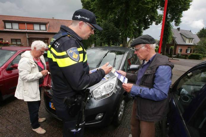 Wijkagent Martin Bekkenk deelt flyers uit voor de Boerenbond in Groesbeek. foto Gerard Verschooten