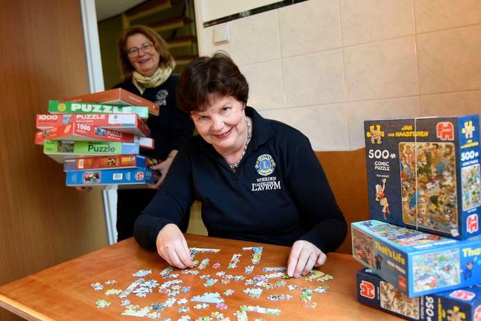 Inge Nederpelt (zittend) en Magda van den Heuvel met puzzels.