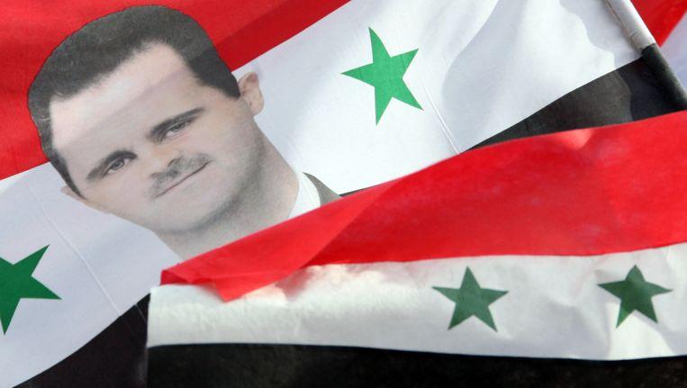 Een vlag met de afbeelding van Assad. Beeld AFP