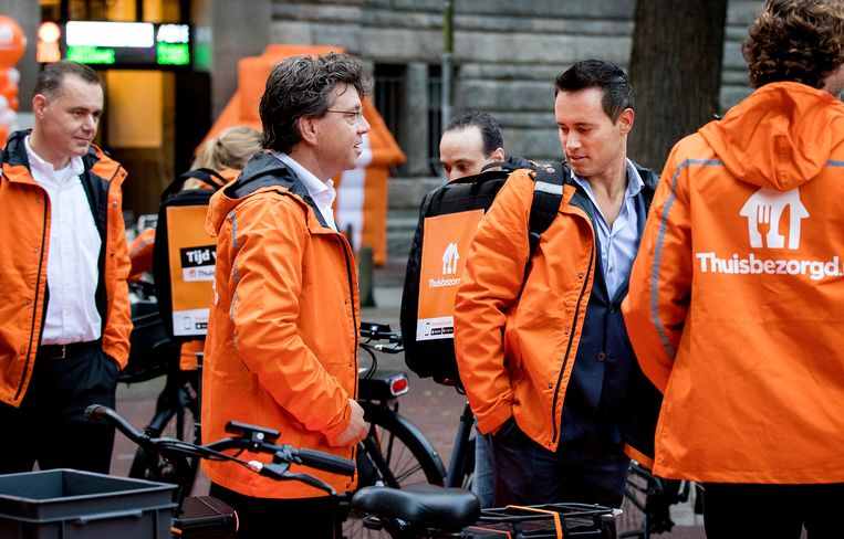 CEO Jitse Groen (tweede van rechts) en personeel van Takeaway komen op de fiets aan bij Beursplein 5. Beeld ANP