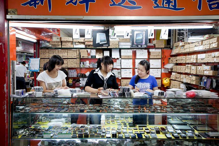 Werknemers van een telefoon accessoire winkel in Shenzhen. Beeld null