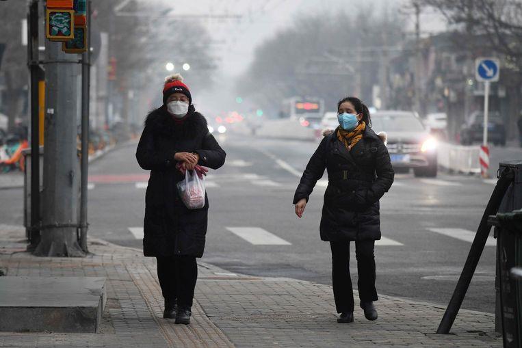 Mondkapjes tegen het coronavirus in Beijing, februari. Volgens het IMF zal de pandemie de wereld in de grootste economische crisis storten sinds de Depressie. Beeld AFP