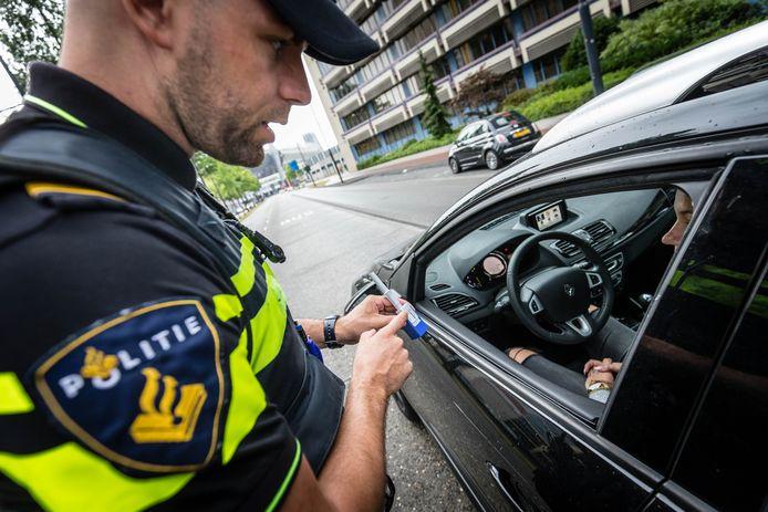 Een agent neemt tijdens een verkeerscontrole een speekseltest af.