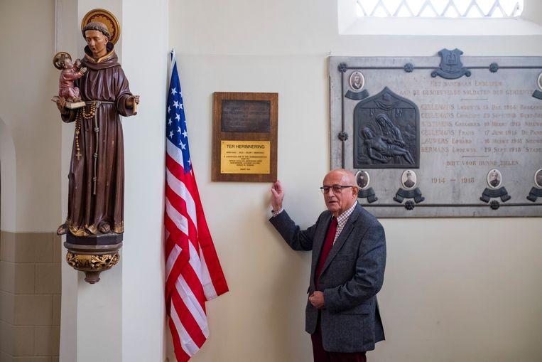 Frans Marivoet bij de gedenkplaat en de Amerikaanse vlag achterin de Sint-Gummaruskerk.
