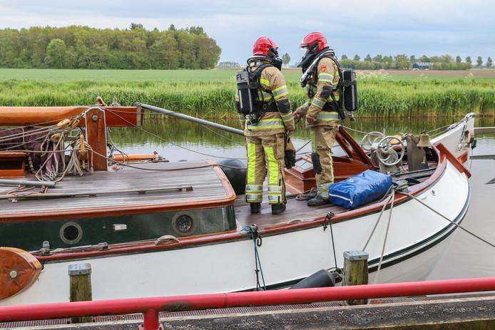 Brandweermannen controleren de 'Alle Winden' in Tollebeek nadat de opvarende naar het ziekenhuis is afgevoerd.