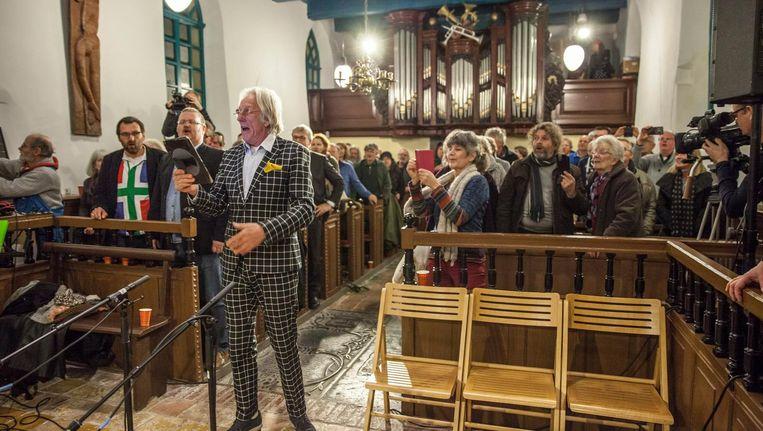Freek de Jonge spiekend op zijn tablet in de kerk in Westernieland. Beeld Harry Cock.