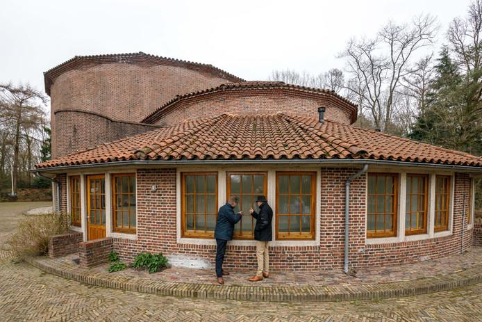 Bert Meijerink en Theo Versteeg spieken door de ramen van de Kunstbunker in Paasloo.