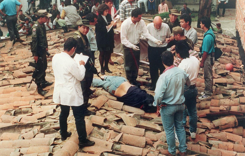 Het lichaam van Pablo Escobar ligt op het dak van een huis in Medellín, op 2 december 1993. Beeld AFP