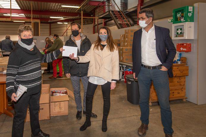 Voedselbank-voorzitter Dorith van Ewijk (l) ontving de waardebonnen en de cheque voor de koelbus uit handen van de raadsleden Laura Waverijn, Stan Meulblok (achter) en Stan Jasperse (r).