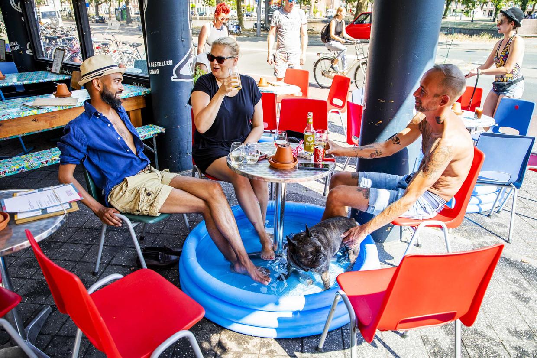 Cafébezoekers vinden op een bloedhete dag in juli van dit jaar verkoeling op een terras aan de Nassaukade in Amsterdam . Beeld ANP