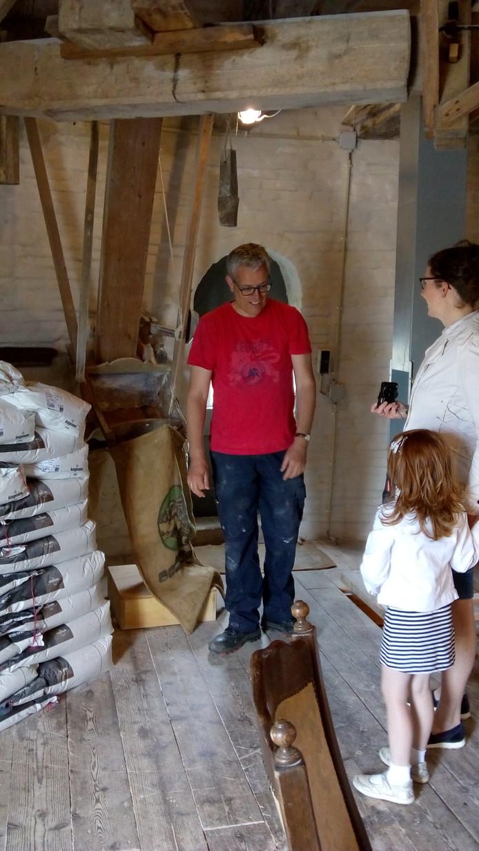 Johan van Rijswijk legt uit hoe het meel hier naar beneden komt aan 2 bezoekers
