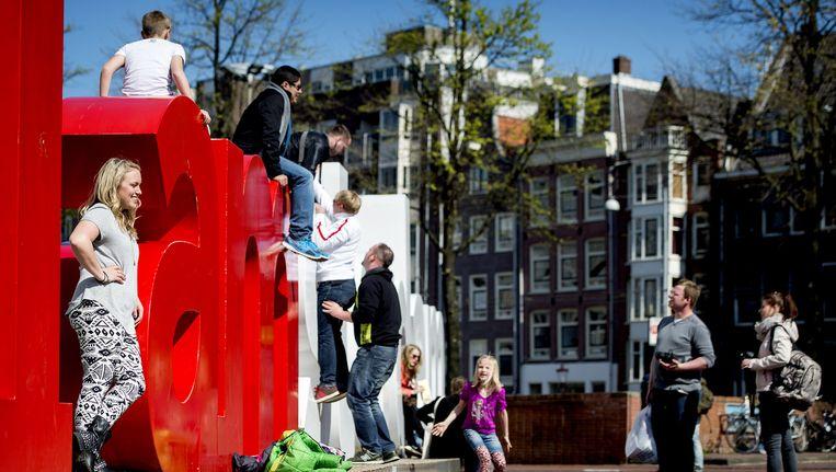 Een meisje gaat op de foto bij het IAmsterdam-logo bij de Stopera. Beeld anp