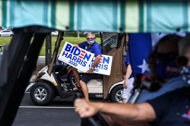 Biden-aanhangers nemen deel aan een parade met golfkarretjes om de nominatie van Joe Biden te vieren als presidentskandidaat voor de Democraten.  Beeld AFP