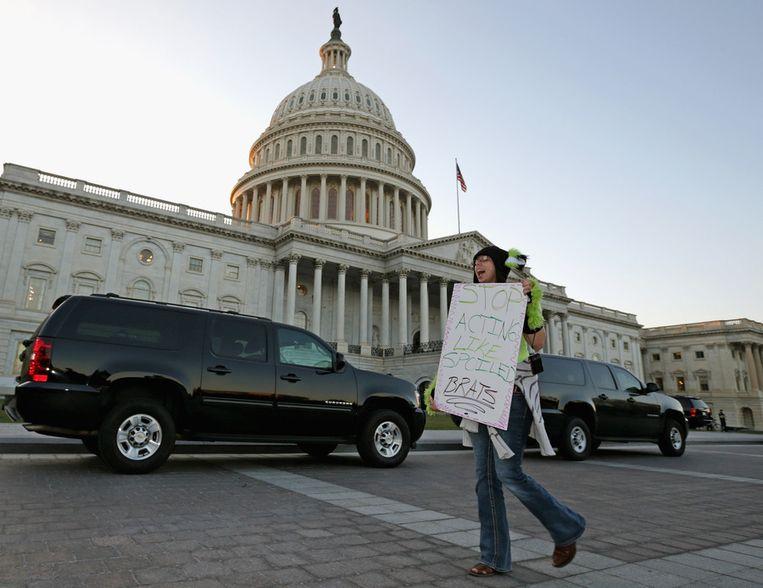 Een vrouw demonstreert maandag voor het Capitool in Washington tegen het onvermogen van de Amerikaanse politici: 'Hou op je te gedragen als verwende ettertjes', staat op haar bord. Beeld afp