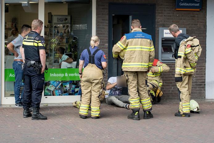 De medewerker van de onderhoudsdienst wordt in de gaten gehouden door brandweerlieden.