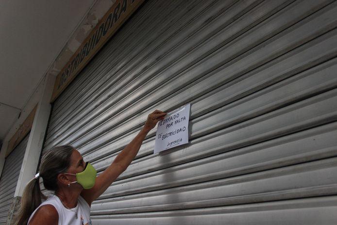 Een vrouw sluit haar winkel in San Cristobal omdat er geen elektriciteit is.