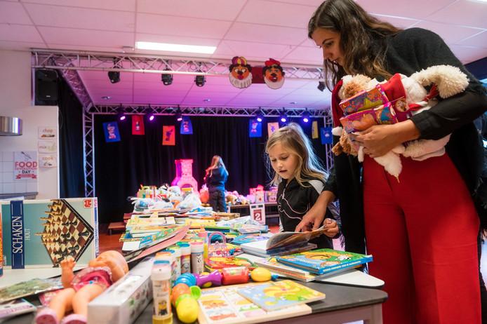 Elisha Keizer zoekt met haar moeder iets leuks uit op de speelgoedruilmarkt, georganiseerd door de International School aan de Joh. ter Horststraat. Slim en duurzaam Sinterklaas vieren door het inbrengen en ruilen van speelgoed: Recycle Sint.
