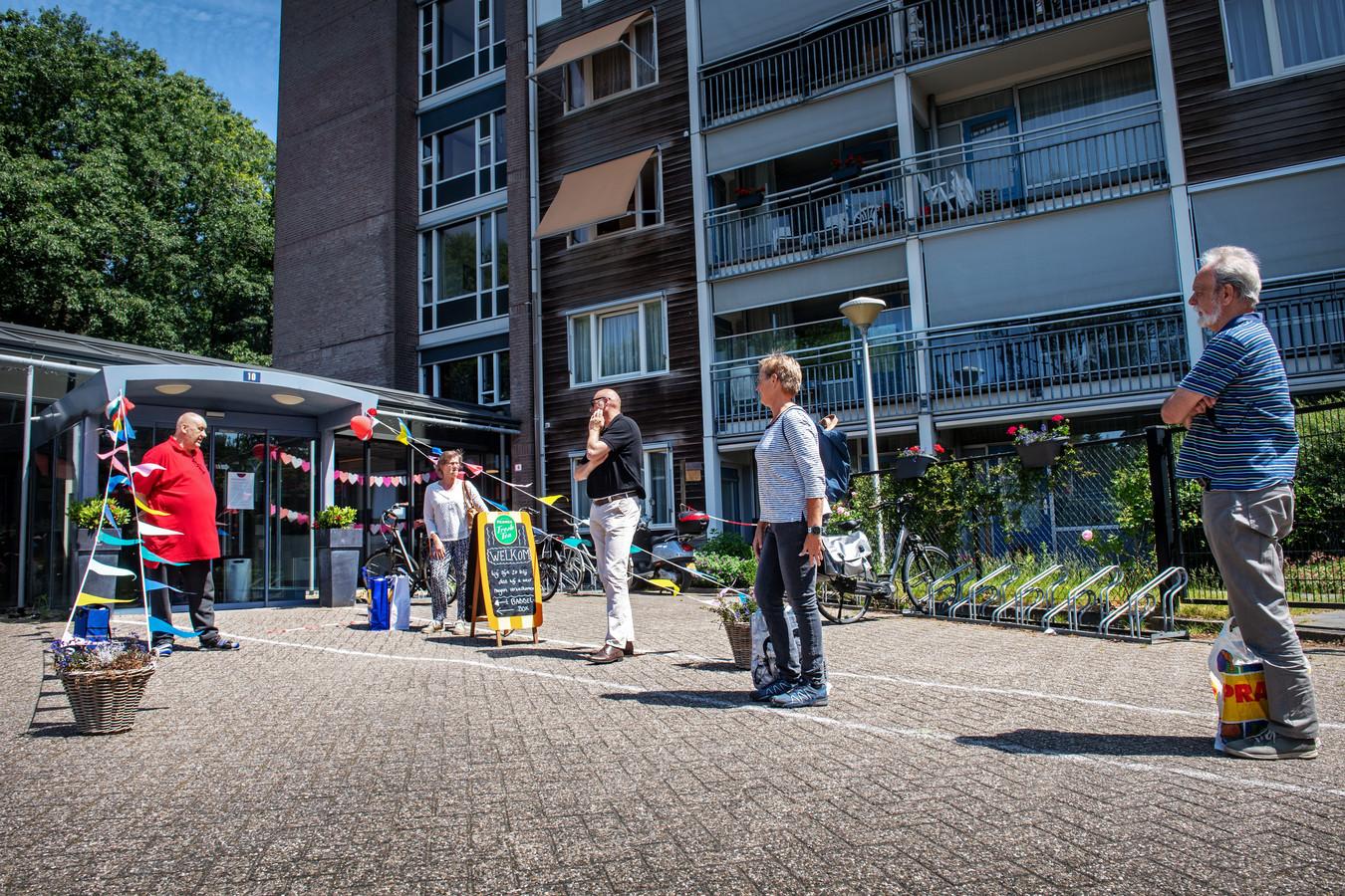 Bezoekers van woonzorgcomplex Boszicht in Nijmegen wachten op hun beurt: één voor één mogen ze naar binnen, om na tien weken eindelijk weer bij hun naasten op visite te mogen.