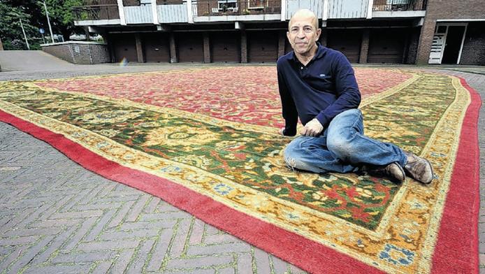 Abbas Babai heeft het kolossale tapijt voor de foto buiten uitgerold
