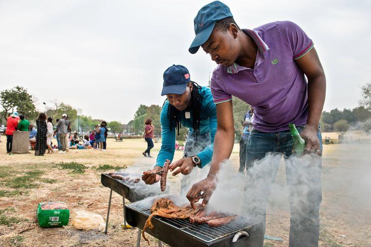 Spencer Chuma (l) en Prince Maseko braaien in park Zoo Lake in Johannesburg. 'Dit is vrijheid. Even je telefoon uit, geen internet, je benauwde stadsappartement uit.' Beeld Bram Lammers