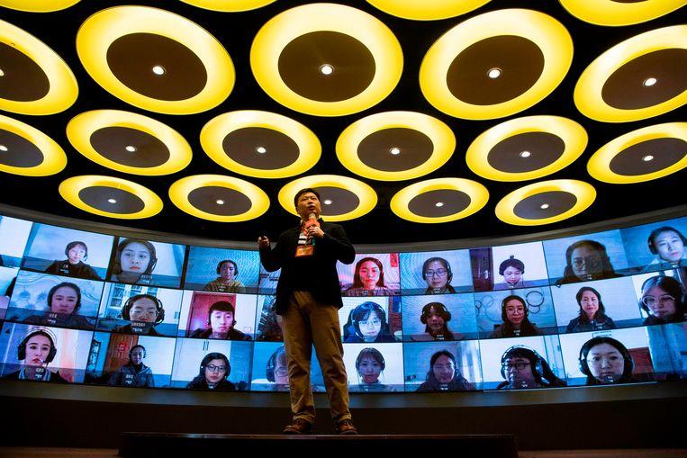 Online is veiliger. Een docent geeft instructies via videoverbinding aan andere docenten hoe ze hun leerlingen online les moeten geven.  Beeld AFP