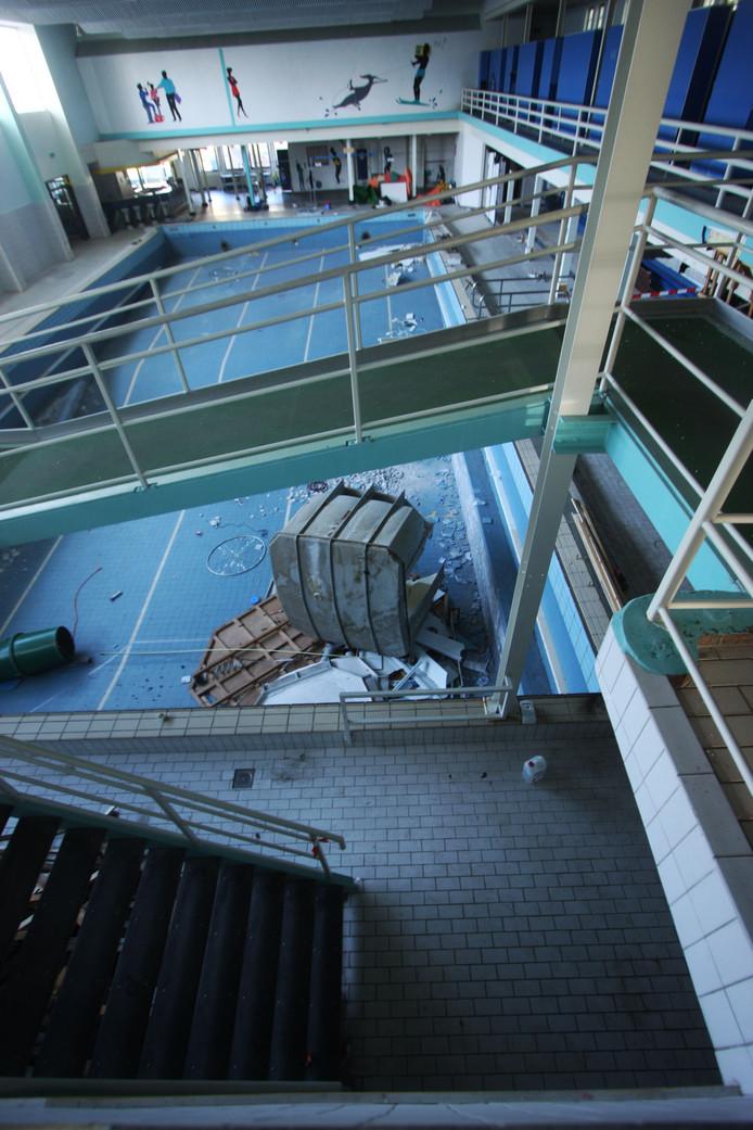 Het diepe bad met de metalen trap naar de glijbaan en kleedruimten.