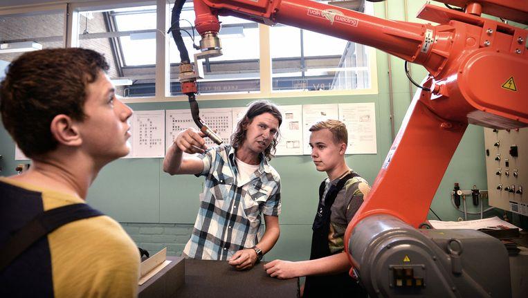 Leerlingen van het Schoonhovens College krijgen uitleg bij een lasrobot, aan de school cadeau gedaan door twee technische bedrijven. Beeld Marcel van den Bergh