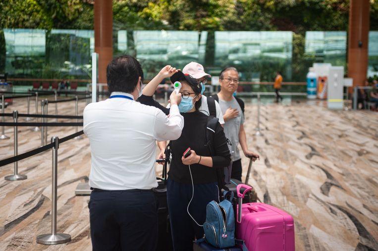 Op vliegvelden is het meten van de lichaamstemperatuur aan de orde van de dag geworden. Zoals hier in de vertrekhal van Singapore. Beeld Photo News
