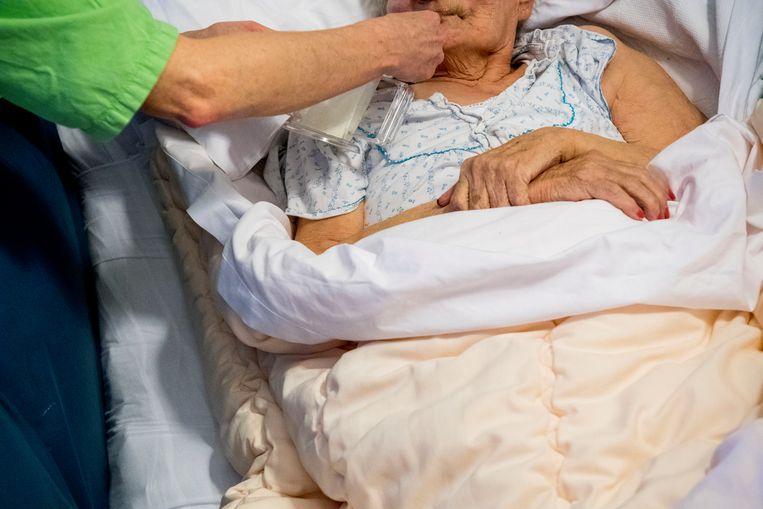 Een medewerker van een verpleeghuis helpt een bewoner met eten.  Beeld ANP XTRA