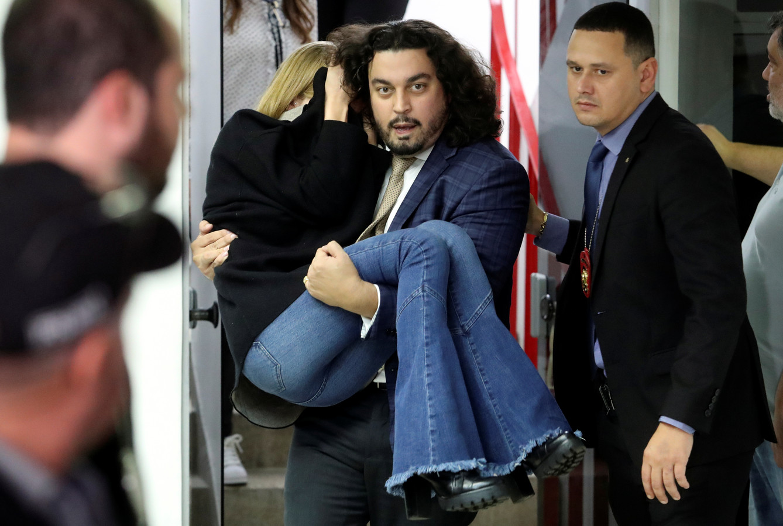 Me Danilo Garcia de Andrade portant Najila Trindade à l'issue de son interrogatoire par la police vendredi dernier.
