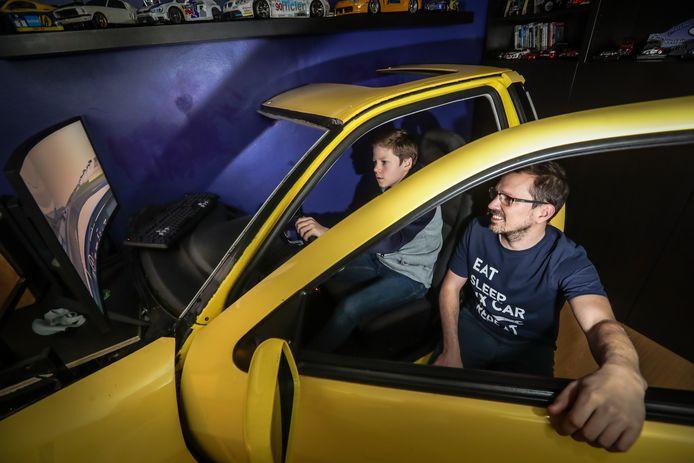 Cliff Haerden kijkt toe hoe zoon Linus de autosimulator uitprobeert.