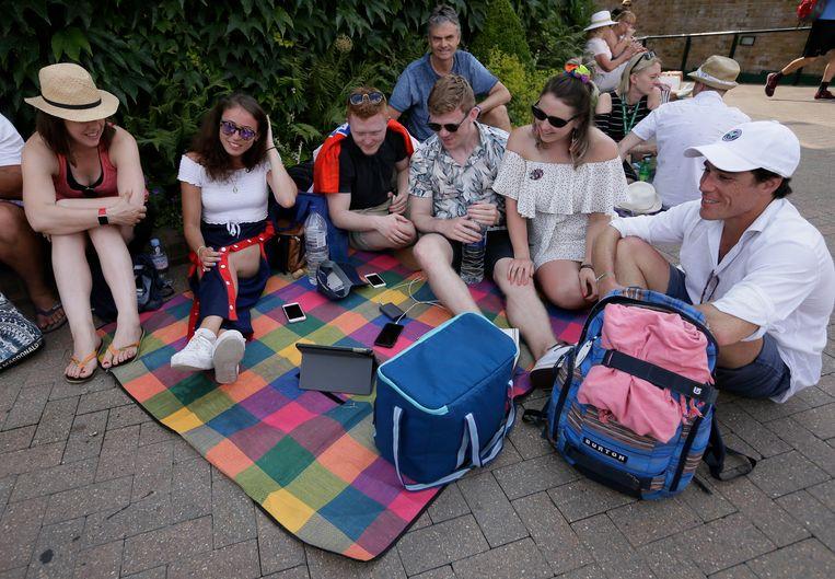 Supporters bekijken de kwartfinale tussen Engeland en Zweden op een tablet op het terrein van Wimbledon. Beeld AP