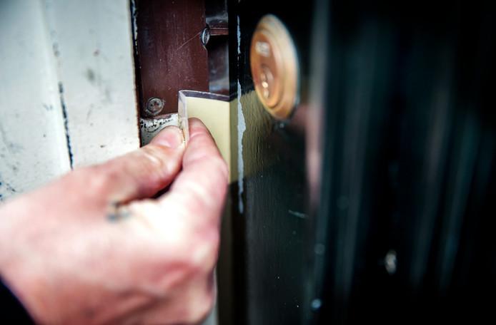 Een inbreker opent met een pasje of een stuk plastic een voordeur. Foto ter illustratie.