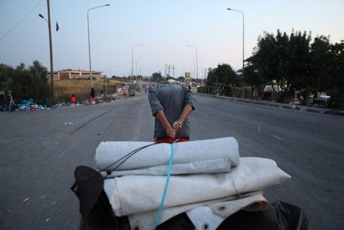 Een man sleept zijn bezittingen naar een nieuw opvangkamp.