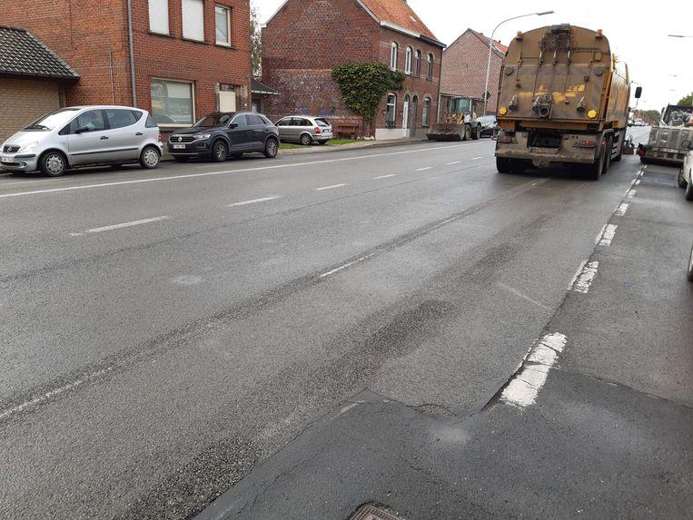 Een machine verwijdert de huidige lijnen van het fietspad op de Meenseweg.